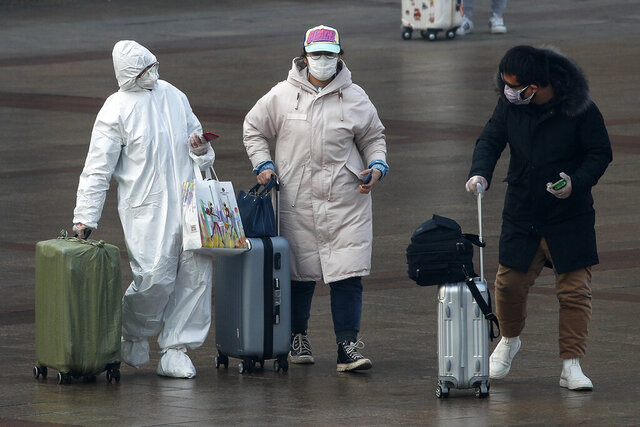 A passenger wearing a full-body protective suit catches the eyes of others as they walk out from the Beijing railway station in Beijing, Tuesday, Feb. 11, 2020. China's daily death toll from a new virus topped 100 for the first time and pushed the total past 1,000 dead, authorities said Tuesday after leader Xi Jinping visited a health center to rally public morale amid little sign the contagion is abating. (AP Photo/Andy Wong)