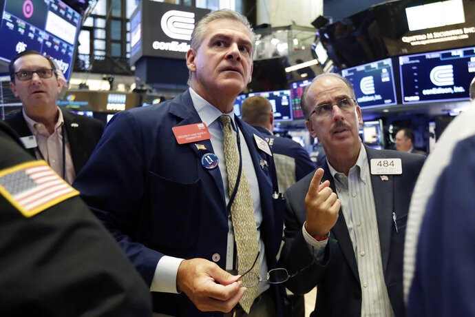 Traders Richard Deviccaro, center, and Joseph Dente, right, work on the floor of the New York Stock Exchange, Friday, Aug. 10, 2018. Stocks are opening moderately lower on Wall Street following steeper losses in Europe, where investors worried about a sharp drop in Turkey's currency. (AP Photo/Richard Drew)