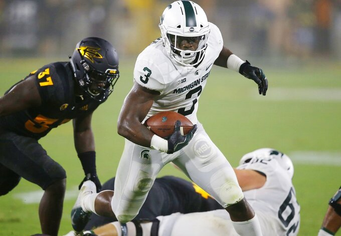 FILE - In this Saturday, Sept. 8, 2018, file photo, Michigan State running back LJ Scott (3) runs past Arizona State linebacker Darien Butler (37) during the first half of an NCAA college football game, in Tempe, Ariz. Scott says he will enter the NFL draft after this season. Scott, a senior, injured his ankle in September and has played in only four games this year. (AP Photo/Ross D. Franklin, File)