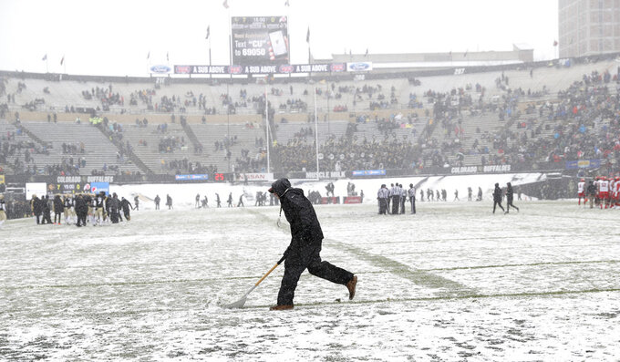 A grounds crew member uses a shovel to clear snow from the yard lines in the first half of an NCAA college football game between Utah and Colorado Saturday, Nov. 17, 2018, in Boulder, Colo. (AP Photo/David Zalubowski)