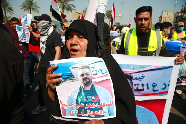 A woman holds a picture of her a missing son during anti-government protest in Baghdad, Iraq, Sunday, Feb. 23, 2020. There are 25 activists still missing since the protests erupted on Oct. 1, 2019, according to the semi-official Iraqi High Commission for Human Rights. No group has claimed responsibility but activists have blamed the militias. Arabic reads,