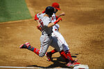 Los Angeles Angels starting pitcher Andrew Heaney, right, beats Boston Red Sox's Andrew Benintendi to first to force him out during the third inning of a baseball game Sunday, Sept. 1, 2019, in Anaheim, Calif. (AP Photo/Mark J. Terrill)