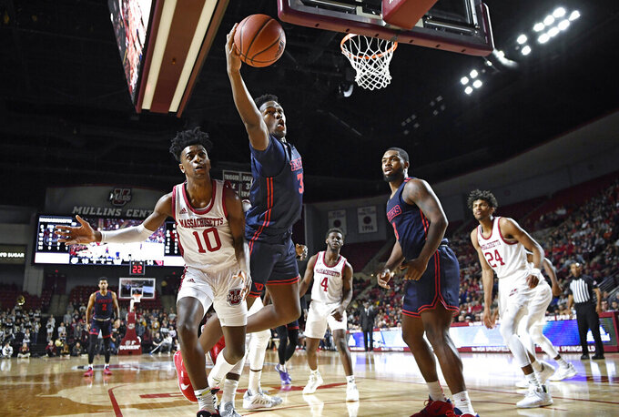 Dayton's Jordy Tshimanga reaches out to keep the ball in play as Massachusetts' Sean East II (10) defends in the first half of an NCAA college basketball game, Saturday, Feb. 15, 2020, in Amherst, Mass. (AP Photo/Jessica Hill)