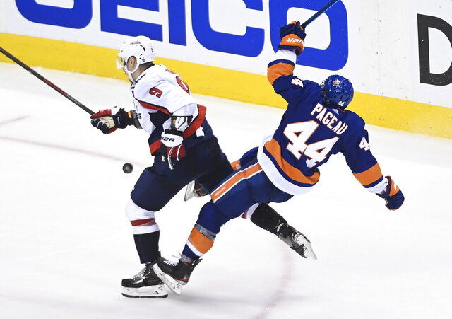 Washington Capitals defenceman Dmitry Orlov (9) hits New York Islanders center Jean-Gabriel Pageau (44) during the third period of an NHL Eastern Conference Stanley Cup playoff hockey game in Toronto, Ontario, on Tuesday, Aug. 18, 2020. (Nathan Denette/The Canadian Press via AP)
