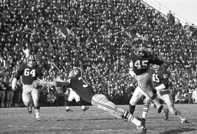FILE - In this Nov. 23, 1968, file photo, Harvard's Pat Conway (34) stretches in vain effort to intercept a Brian Dowling pass meant for Calvin Hill, not shown, as the ball got past Harvard's Tom Wynne, (45), in the second period of a college football game at Harvard Stadium in Cambridge, Mass. Harvard's Gary Farneti, (64), is at left. Sixty-five members of Harvard's 1968 football team are expected back on campus this weekend for the 50th anniversary of The Game's most memorable edition.  (AP Photo/A.E. Maloof, File)