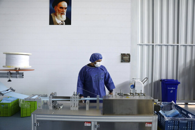 Under a portrait of the late Iranian revolutionary founder Ayatollah Khomeini, a worker wearing a protective suit controls a machine which makes face masks at a factory in Eshtehard, some 70 miles (114 kilometers) west of the capital Tehran, Iran, Tuesday, April 14, 2020. The factory is producing protective masks round-the-clock in a fight against the new coronavirus to meet the domestic demand as the country faces the worst outbreak in the Middle East. (AP Photo/Vahid Salemi)