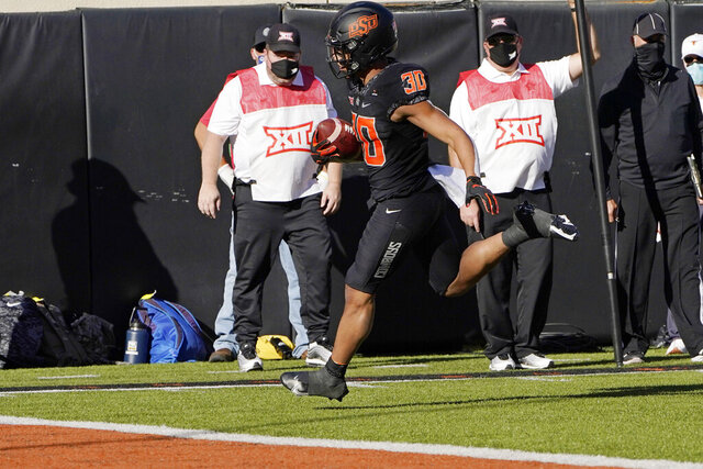 Oklahoma State running back Chuba Hubbard (30) carries a Spencer Sanders pass into the end zone all alone for a touchdown during the first half of the team's NCAA college football game against Texas in Stillwater, Okla., Saturday, Oct. 31, 2020. (AP Photo/Sue Ogrocki)