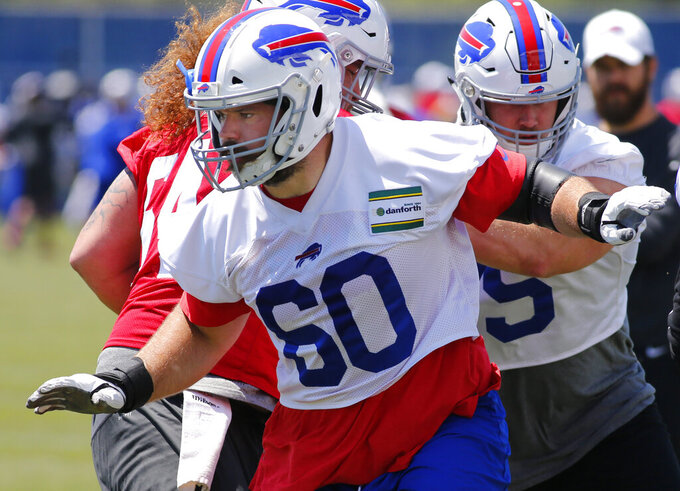In this June 11, 2019 photo Buffalo Bills offensive linemen Mitch Morse (60) runs drills during an NFL football team practice in Orchard Park N.Y. Morse has such a level-headed approach about him, the Bills new starting center likes to recount how he was usually the one asked to address the media after losses during his previous four seasons in Kansas City. It's not exactly a point of pride for him, because he hated losing as much as anyone. And it's not to suggest he was attempting to seek out the spotlight. Morse instead brought up his past role in putting losses into perspective after being complimented on his calming ability to put people at ease. (AP Photo/Jeffrey T. Barnes)