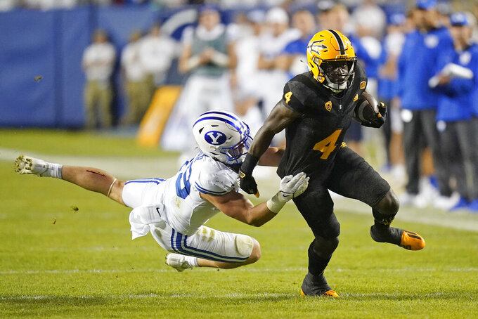 Arizona State running back Daniyel Ngata (4) breaks free from a tackle by BYU linebacker Payton Wilgar (49) in the second half during an NCAA college football game Saturday, Sept. 18, 2021, in Provo, Utah. (AP Photo/Rick Bowmer)