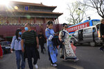 Residents in traditional costumes leave from a side entrance to the Forbidden City where a bus offers free coronavirus vaccinations in Beijing on Wednesday, April 14, 2021. China's success at controlling the outbreak has resulted in a population that has seemed almost reluctant to get vaccinated. Now, it is accelerating its inoculation campaign by offering incentives — free eggs, store coupons and discounts on groceries and merchandise — to those getting a shot. (AP Photo/Ng Han Guan) hoto/Ng Han Guan)