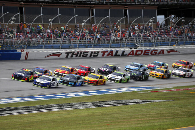 William Byron (24) and Ryan Blaney (12) lead the pack to restart after rain delayed a NASCAR Cup Series auto race at Talladega Superspeedway, Monday, Oct 14, 2019, in Talladega, Ala. (AP Photo/Butch Dill)
