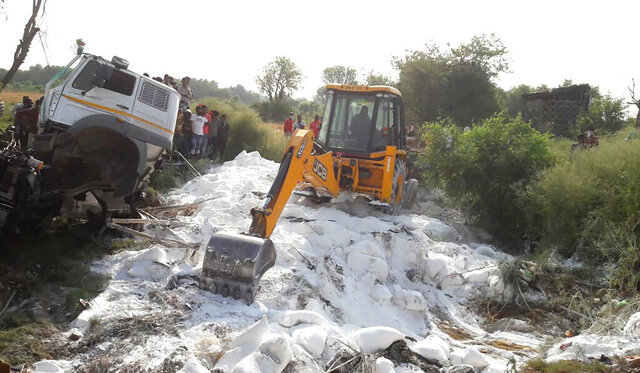 An excavator clears bags of white cement scattered on a road after a truck accident near Auraiya, a village in Uttar Pradesh state, India, Saturday, May 16, 2020. At least 23 migrant workers were killed early Saturday when a truck they were travelling in crashed into a stationary truck on a highway in northern India, an official said. Tens of thousands of migrant laborers have been returning from big cities to their villages after losing jobs because of a countrywide lockdown imposed in late March to contain the spread of the coronavirus. (AP Photo)