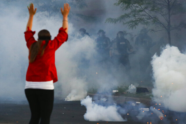 Tear gas canisters detonate beside a protester as authorities clear an intersection near the Minneapolis 5th Police Precinct, Saturday, May 30, 2020, in Minneapolis. Protests continued following the death of George Floyd, who died after being restrained by Minneapolis police officers on Memorial Day. (AP Photo/John Minchillo)