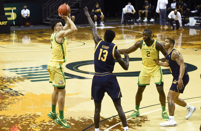 Oregon guard Chris Duarte (5) shoots a 3-pointer over California forward Kuany Kuany (13) as Oregon forward Eugene Omoruyi (2) and California guard Matt Bradley (20) stand nearby during the second half of an NCAA college basketball game Thursday, Dec. 31, 2020, in Eugene, Ore. (AP Photo/Andy Nelson)