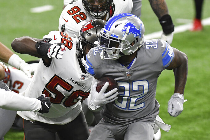 Detroit Lions running back D'Andre Swift (32) is chased by Tampa Bay Buccaneers outside linebacker Shaquil Barrett (58) during the first half of an NFL football game, Saturday, Dec. 26, 2020, in Detroit. (AP Photo/Lon Horwedel)
