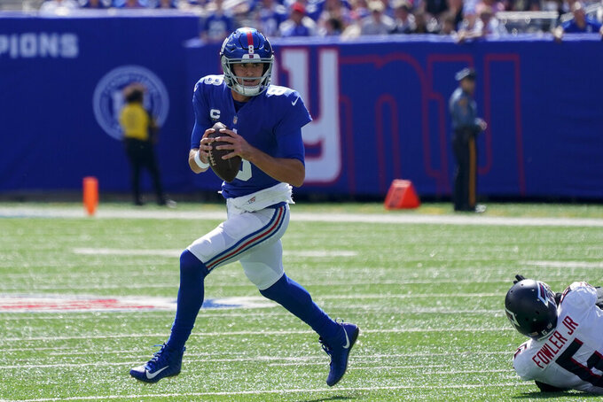New York Giants quarterback Daniel Jones (8) looks to pass after breaking away from Atlanta Falcons defensive end Dante Fowler Jr. (6) during the first half of an NFL football game, Sunday, Sept. 26, 2021, in East Rutherford, N.J. (AP Photo/Seth Wenig)