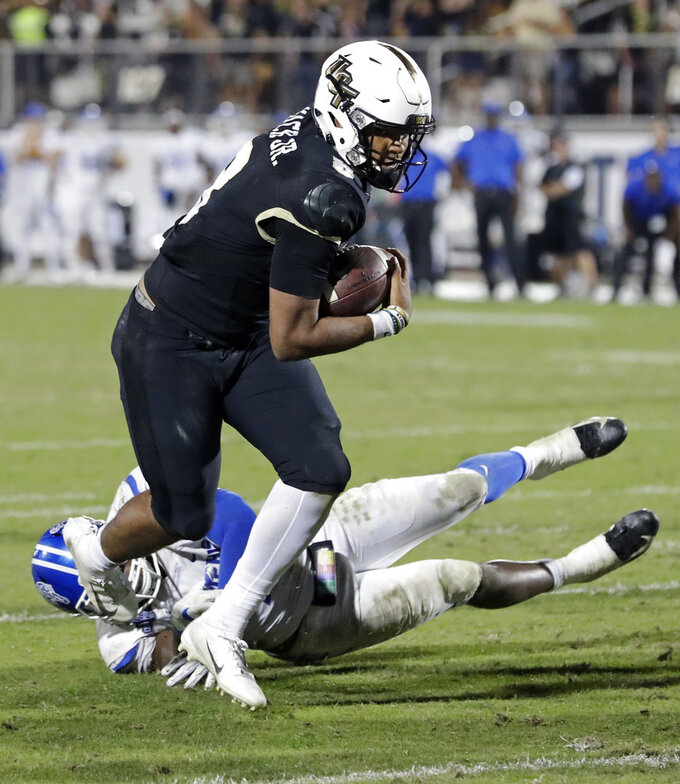 Central Florida quarterback Darriel Mack Jr., left, runs past Memphis linebacker Curtis Akins for a touchdown on a 2-yard run during the second half of the American Athletic Conference championship NCAA college football game, Saturday, Dec. 1, 2018, in Orlando, Fla. (AP Photo/John Raoux)