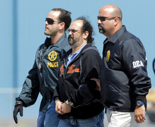 FILE - In this May 13, 2008 file photo, Colombian paramilitary Rodrigo Tovar, center, is escorted by U.S. DEA Agents at his arrival in Opa-locka, Florida. Tovar, also known as Jorge 40, was flown back to his home country on a deportation flight, Monday, Sept. 28, 2020, after spending twelve years in U.S. prisons for drug trafficking, the National Commissioner for Peace Miguel Ceballos said. (AP Photo/Alan Diaz, File)