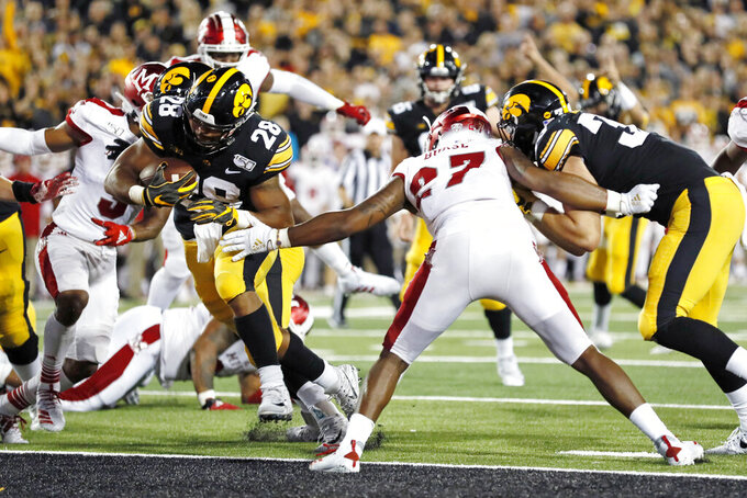 Iowa running back Toren Young scores on a 2-yard touchdown run in front of Miami of Ohio linebacker Kobe Burse (27) during the second half of an NCAA college football game, Saturday, Aug. 31, 2019, in Iowa City, Iowa. Iowa won 38-14. (AP Photo/Charlie Neibergall)