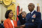 Gen. Charles Q. Brown Jr., is sworn is as Chief of Staff of the Air Force as his wife Sharene Guilford Brown, holds a bible, in the Oval Office of the White House, Tuesday, Aug. 4, 2020, in Washington. (AP Photo/Alex Brandon)