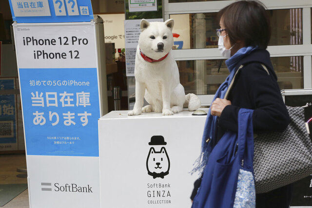 People walk by a SoftBank shop in Tokyo, Monday, Nov. 9, 2020. Japanese technology company SoftBank Group Corp. said Monday it restored its profitability in the last quarter as its investments improved in value. (AP Photo/Koji Sasahara)