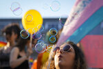 Buildings are reflected in soap balloons during the Bucharest Pride 2021 in Bucharest, Romania, Saturday, Aug. 14, 2021. The 20th anniversary of the abolishment of Article 200, which authorized prison sentences of up to five years for same-sex relations, was one cause for celebration during the gay pride parade and festival held in Romania's capital this month. People danced, waved rainbow flags and watched performances at Bucharest Pride 2021, an event that would have been unimaginable a generation earlier. (AP Photo/Vadim Ghirda)