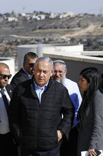 Israeli Prime Minister Benjamin Netanyahu, center, and heads of Israeli settlement authorities tour the Alon Shvut settlement, in the Gush Etzion block, in the occupied the West Bank, Tuesday, Nov. 19, 2019. Netanyahu traveled to the West Bank to celebrate the U.S.'s announcement that it does not consider Israeli settlements to be a violation of international law. (Menahem Kahana/Pool via AP)