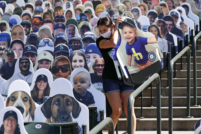 Seattle Mariners worker Lindsay Garza carries cutouts of fans to place in seats at the team's ballpark as part of the