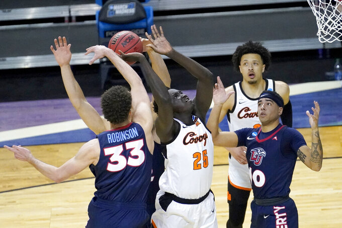 Liberty's Shiloh Robinson (33) blocks the shot of Oklahoma State forward Bernard Kouma (25) during the first half of a first round NCAA college basketball game Friday, March 19, 2021, at the Indiana Farmers Coliseum in Indianapolis.(AP Photo/Charles Rex Arbogast)