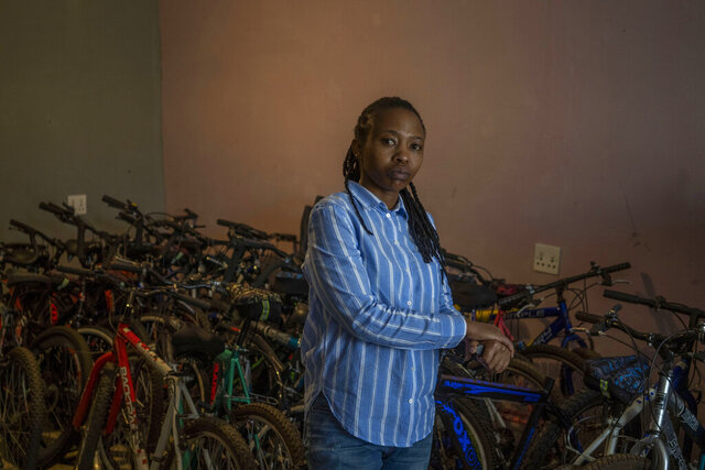 In this Friday May 1, 2020 photo, 34-year-old entrepreneur Fino Dlamini poses for a photograph inside her office in the Soweto township outside Johannesburg, South Africa.  Business was good in January and February, and projections for the rest of 2020 were excellent. Then the coronavirus brought everything to an abrupt halt. Dlamini was confined to her small home under a strict lockdown, with few options for earning money. South Africa is struggling to balance its fight against the coronavirus with its dire need to resume economic activity. The country with the Africa's most developed economy also has its highest number of infections — more than 19,000.  (AP Photo/Bram Janssen)