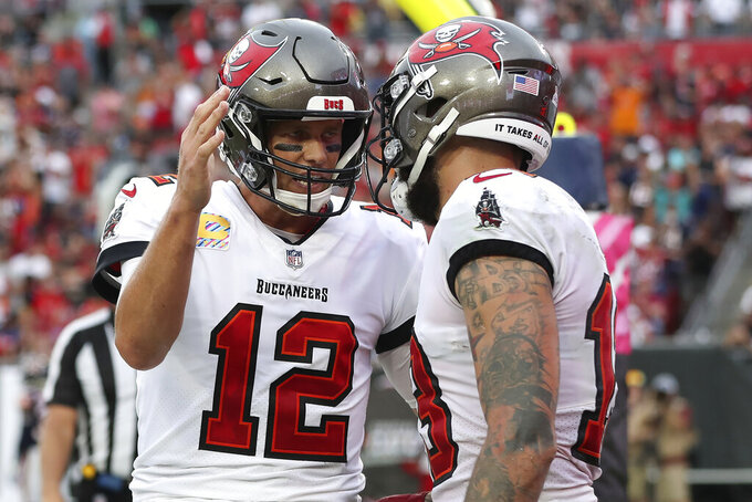Tampa Bay Buccaneers quarterback Tom Brady (12) celebrates with wide receiver Mike Evans (13) after Evans couaght a touchdown pass during the first half of an NFL football game against the Chicago Bears Sunday, Oct. 24, 2021, in Tampa, Fla. (AP Photo/Mark LoMoglio)