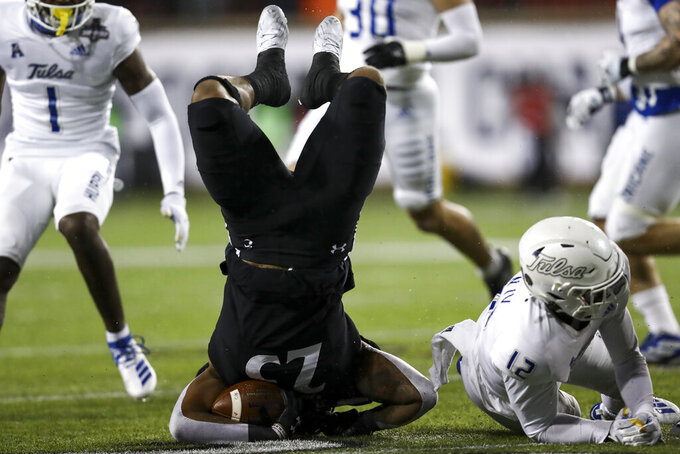 Cincinnati running back Cameron Young, left, is tackled by Tulsa cornerback Allie Green IV, right, during the first half of the American Athletic Conference championship NCAA college football game, Saturday, Dec. 19, 2020, in Cincinnati. (AP Photo/Aaron Doster)