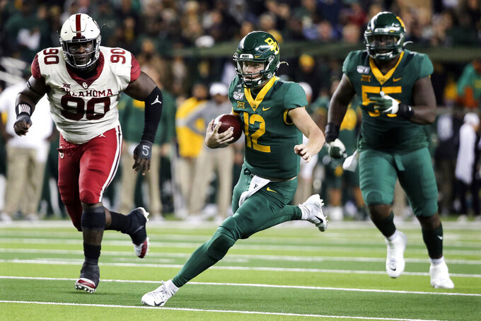 Baylor quarterback Charlie Brewer (12) carries the ball as he is chased by Oklahoma defensive lineman Neville Gallimore (90) during the first half of an NCAA college football game in Waco, Texas, Saturday, Nov. 16, 2019. (AP Photo/Ray Carlin)