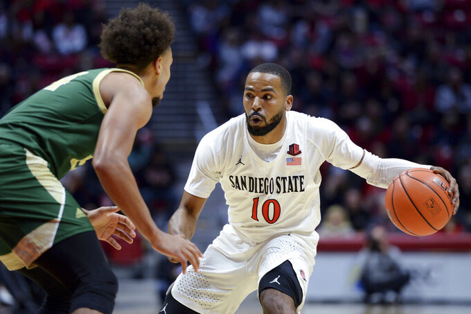 San Diego State guard KJ Feagin (10) dribbles the ball while defended by Cal Poly guard Junior Ballard during the first half of an NCAA college basketball game Saturday, Dec. 28, 2019, in San Diego. (AP Photo/Orlando Ramirez)