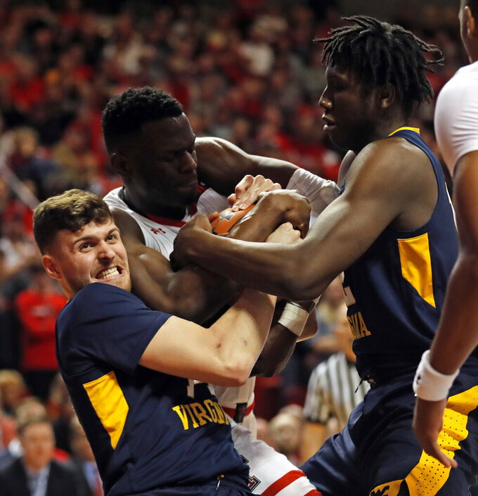West Virginia's Chase Harler (14), Andrew Gordon (12) and Texas Tech's Norense Odiase (32) fight for control of the ball during the first half of an NCAA college basketball game Monday, Feb. 4, 2019, in Lubbock, Texas. (AP Photo/Brad Tollefson)