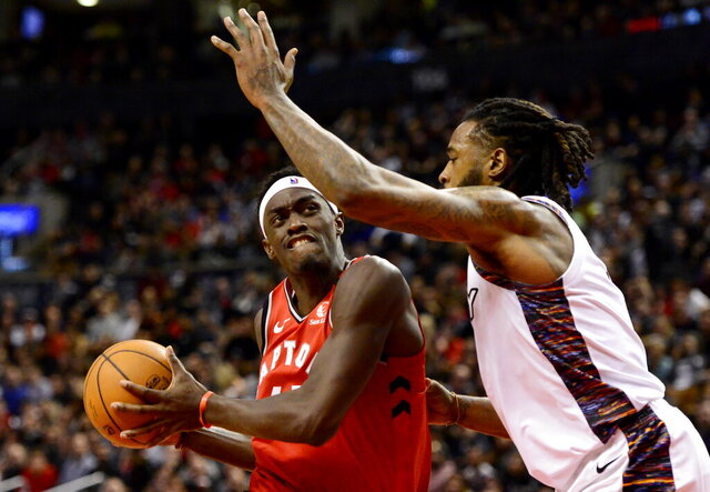 Toronto Raptors forward Pascal Siakam, left, is defended by Brooklyn Nets forward Taurean Prince (2) during the second half of an NBA basketball game Saturday, Feb. 8, 2020, in Toronto. (Frank Gunn/The Canadian Press via AP)