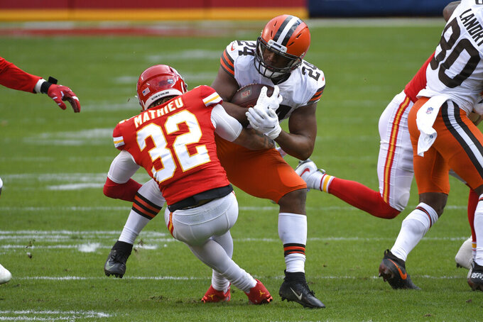Cleveland Browns running back Nick Chubb (24) is tackled by Kansas City Chiefs safety Tyrann Mathieu (32) during the first half of an NFL divisional round football game, Sunday, Jan. 17, 2021, in Kansas City. (AP Photo/Reed Hoffmann)
