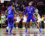 Kansas' Marcus Garrett (0) and Isaiah Moss (4) slap hands during the first half of the team's NCAA college basketball game against Oklahoma in Norman, Okla., Tuesday, Jan. 14, 2020. (AP Photo/Garett Fisbeck)