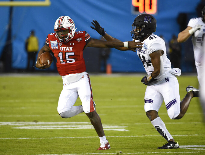 Utah quarterback Jason Shelley (15) runs away from Northwestern safety Jared McGee (41) on his way to a first down during the first half of the Holiday Bowl NCAA college football game Monday, Dec. 31, 2018, in San Diego. (AP Photo/Denis Poroy)