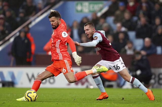 Watford goalkeeper Ben Foster clears under pressure from Aston Villa's Indiana Vassilev during the English Premier League match at Villa Park, Birmingham, England, Tuesday Jan. 21, 2020. (David Davies/PA via AP)