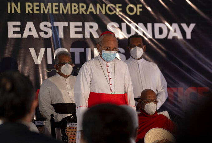 FILE- In this April 21, 2021 file photo, Cardinal Malcolm Ranjith, archbishop of Colombo, center, observes two minute silence for the victims of 2019 Easter Sunday attacks during a service at St. Anthony's Church in Colombo, Sri Lanka,  Sri Lankan President Gotabaya Rajapaksa has ordered an investigation of allegations that some members of state intelligence agencies knew and met with people who carried out Easter Sunday bombings in 2019 that killed more than 260 people, a government official said. (AP Photo/Eranga Jayawardena, File)