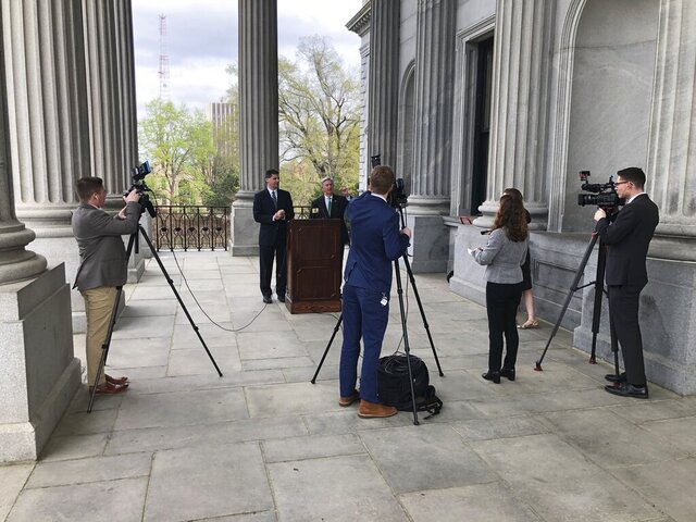 Republican state Sen. Shane Massey of Edgefield, left, and Democratic State Sen. Nikki Setzler, right, speak to reporters outside the South Carolina Statehouse on Tuesday, March 17, 2020, in Columbia, S.C. The senators and reporters wanted to practice social distancing for the news conference. (AP Photo / Jeffrey Collins)