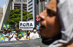 """Demonstrators hold a sign in Portuguese that reads """"Bolsonaro out,"""" during a protest against Brazilian President Jair Bolsonaro, at Paulista Avenue, Sao Paulo, Brazil, Sunday, Sep. 12, 2021. (AP Photo/Marcelo Chello)"""