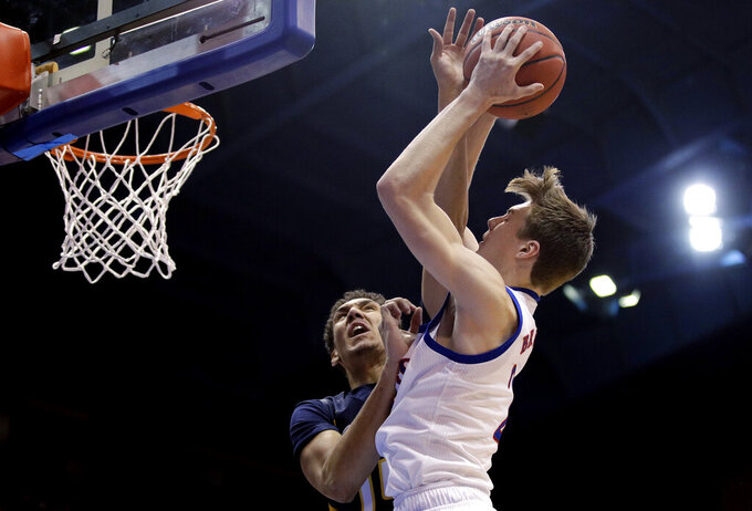 UNC Greensboro's Kyrin Galloway, left, tries to block a shot by Kansas' Christian Braun during the first half of an NCAA college basketball game Friday, Nov. 8, 2019, in Lawrence, Kan. (AP Photo/Charlie Riedel)