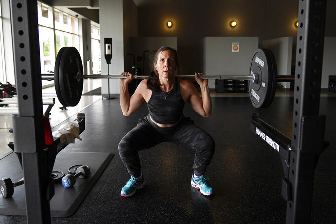 Angela Fitzgerald, of Bloomfield Hills., exercises at Burn Fitness in Rochester Hills, Mich., Monday, June 21, 2021. Michigan is fully open again. After facing 15 months of capacity restrictions and being hit by the country's worst surge of coronavirus infections this spring, restaurants, entertainment businesses and other venues can operate at 100% occupancy starting Tuesday. (AP Photo/Paul Sancya)