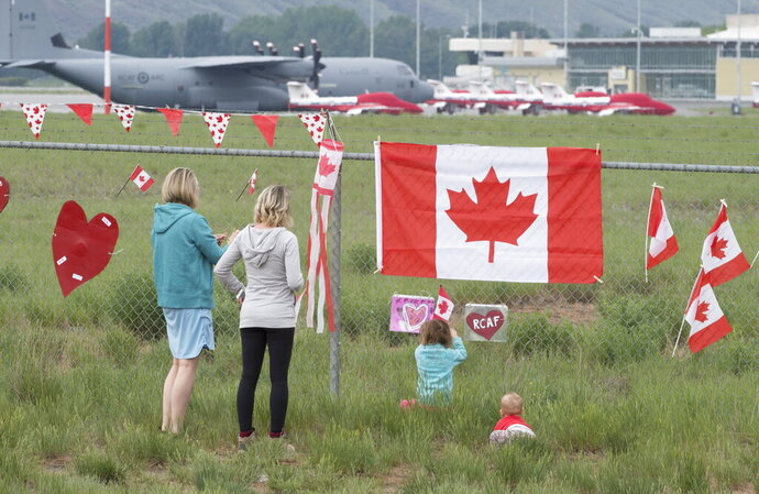 The Canadian Forces Snowbirds jets are seen in the background as a family pays their respects in Kamloops, B.C., Monday, May 18, 2020. Capt. Jenn Casey died Sunday after the Snowbirds jet she was in crashed shortly after takeoff. The pilot of the aircraft is in hospital with serious injuries. (Jonathan Hayward/The Canadian Press via AP)