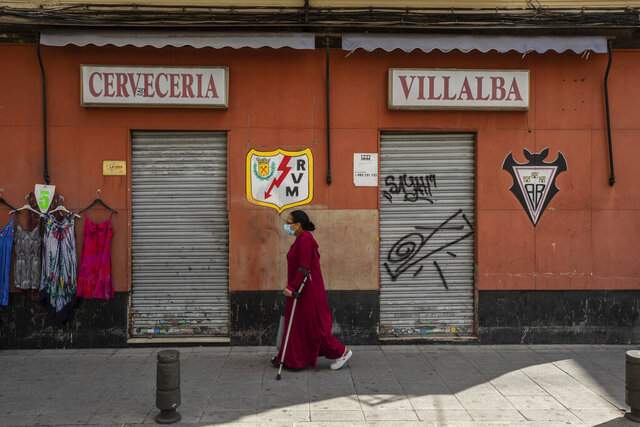 A woman wearing a face mask to prevent the spread of coronavirus walks in the southern neighbourhood of Vallecas in Madrid, Spain, Monday, Sept. 21, 2020. Police in the Spanish capital and its surrounding towns are stopping people coming in and out of some working-class neighborhoods that have been partially locked down to stem Europe's fastest coronavirus spread. Heightened restrictions to stem Europe's fastest coronavirus spread in some of Madrid's working-class neighborhoods brought a heated debate over the prevalence of inequality in Spain back into the spotlight Monday. (AP Photo/Bernat Armangue)