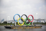 IN thios Aug. 6, 2020, file photo, the Olympic rings for the Olympic and Paralympic Games Tokyo 2020 pass by on a barge by tugboats off the Odaiba Marine Park in Tokyo. It's been six months since the Tokyo Olympics were postponed until next year by the COVID-19 pandemic. Everyone from new Japan Prime Minister Yoshihide Suga to IOC President Thomas Bach have tried to assure the Japanese public and deep-pocketed sponsors that the Olympics will take place. (AP Photo/Hiro Komae, File)