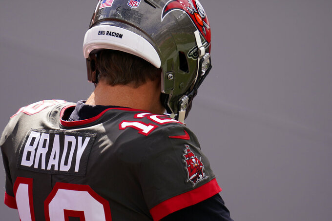 """Tampa Bay Buccaneers quarterback Tom Brady wears the words, """"end racism"""" on his helmet before an NFL football game against the Denver Broncos, Sunday, Sept. 27, 2020, in Denver. (AP Photo/David Zalubowski)"""