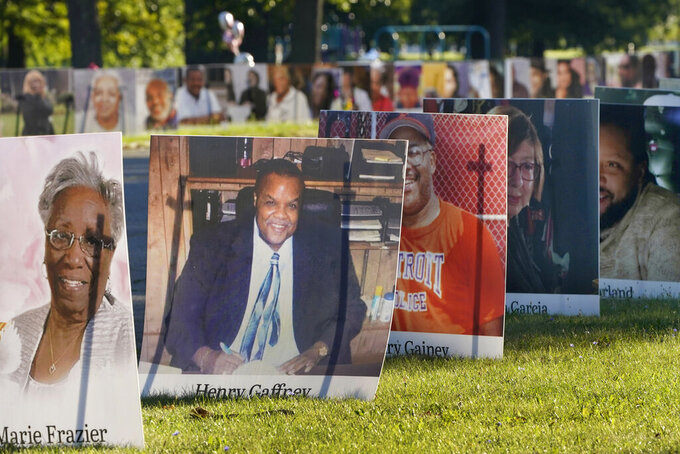 FILE - In this Aug. 31, 2020, file photo, some of the nearly 900 large poster-sized photos of Detroit victims of COVID-19 are displayed on Belle Isle in Detroit. The U.S. death toll from the coronavirus topped 200,000 Tuesday, Sept. 22, a figure unimaginable eight months ago when the scourge first reached the world's richest nation with its sparkling laboratories, top-flight scientists and towering stockpiles of medicines and emergency supplies. (AP Photo/Carlos Osorio, File)